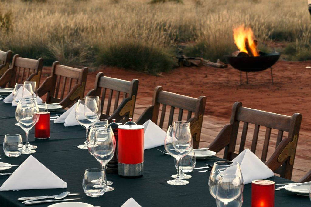 A table and chairs with a fine dining layout, outside with a fire in the background