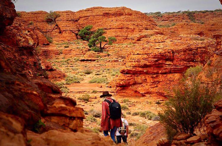 A couple hiking through red cliffs