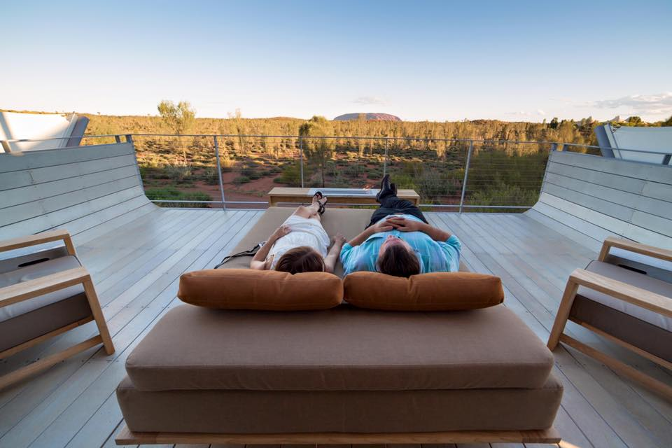 A couple lounging on a bed and looking at the landscape of Australia