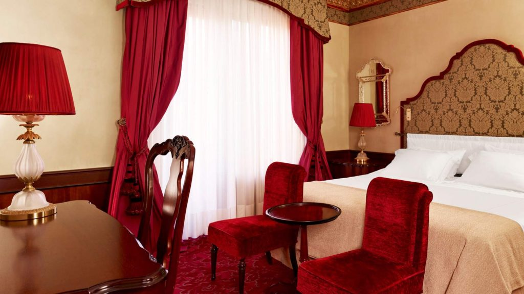 The luxury double room at the hotel Danieli, the room décor merges classical Venetian and dramatic Gothic aesthetic with gilt molding and etched mirror frames.