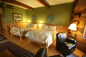 large room with 2 beds in the Deluxe Junior Suite at the Trout Point Lodge in Nova Scoatia