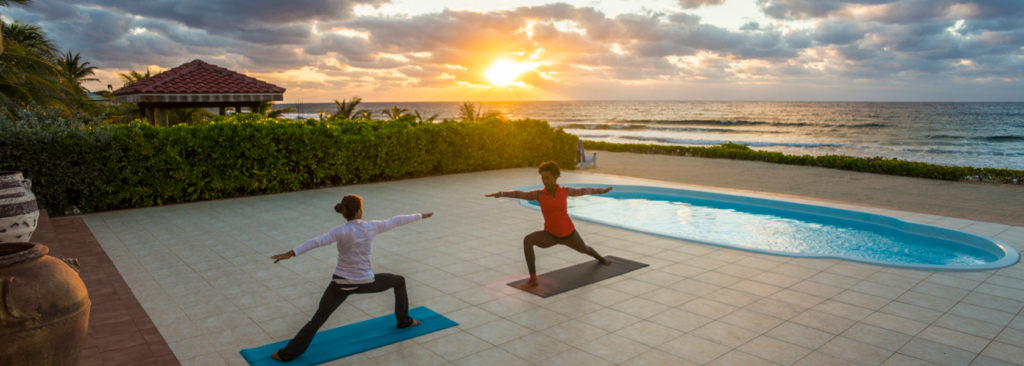 women doing yoga by a pool at the Le Soleil d'Or, Cayman Islands