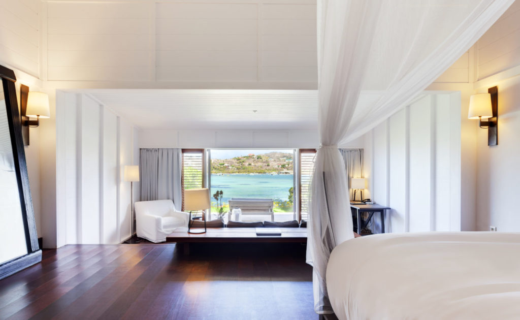 Bedroom in Le Sereno hotel; dark hardwood floors with white accents