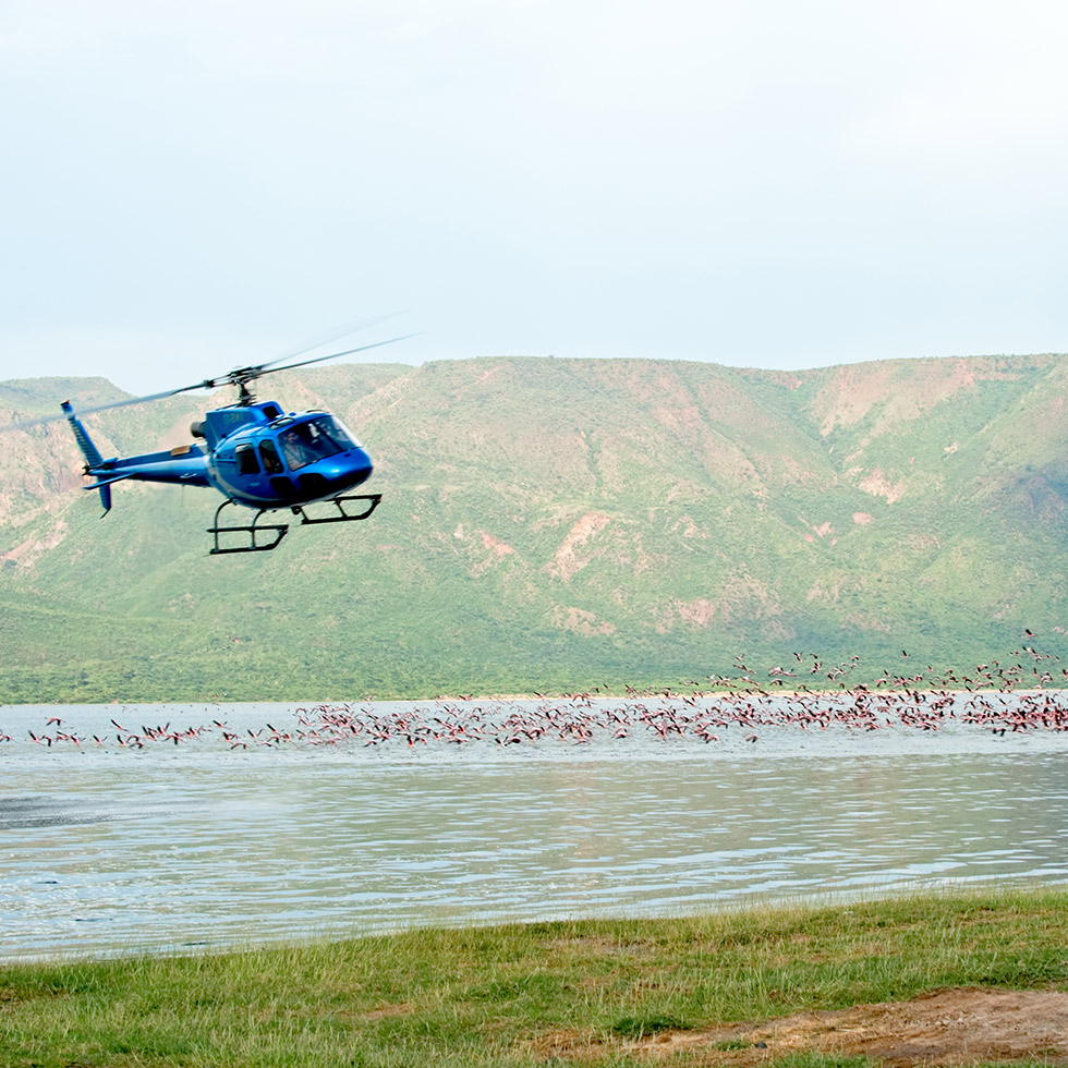 Helicopter landing on the water outside the Segera Retreat in Laikipia, Kenya