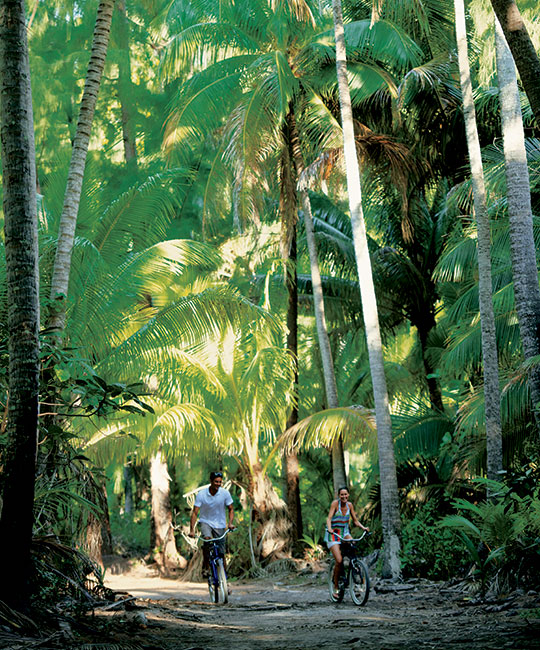 couple biking through a forest on tetiaroa island