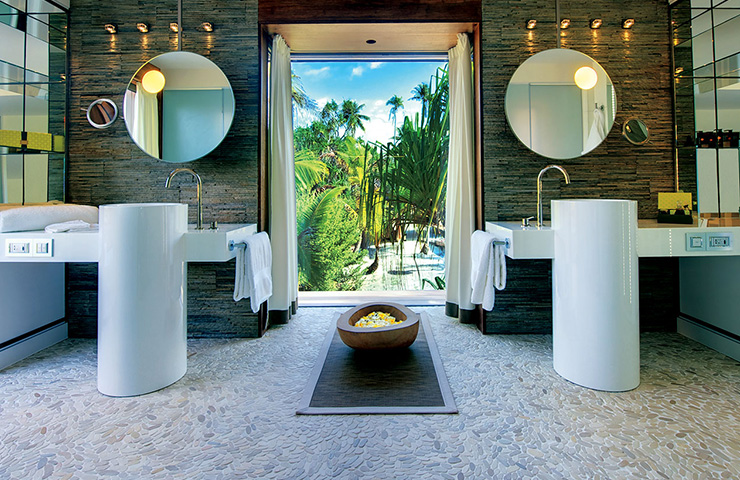 his and hers sinks with circle mirrors looking out among the island of tetiaroa