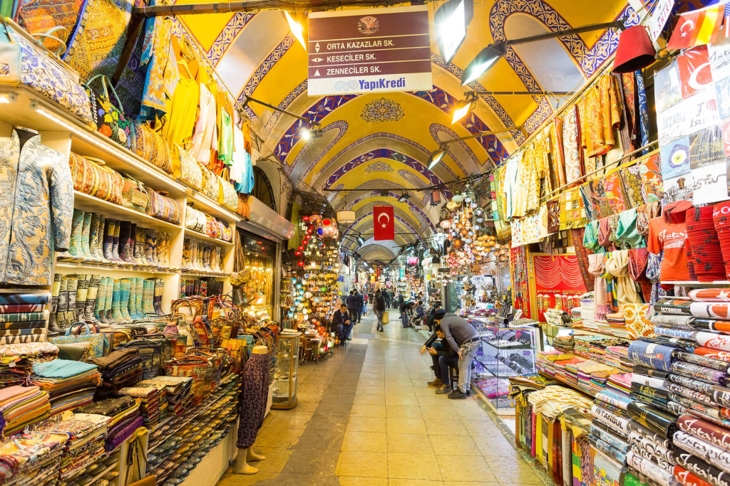 Covered Street Mall Grand Bazaar in Istanbul Turkey with shoppers in the distance and stores along the sides