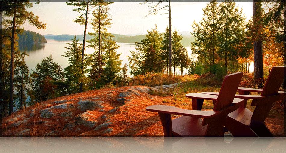 Two empty wooden chairs with a tree-obstructed view of lake saranac at The Point Resort