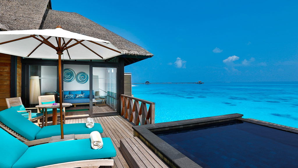 Two lounge chairs and umbrella on the deck of a villa at JA Manafaru in Maldives looking out over the Indian Ocean