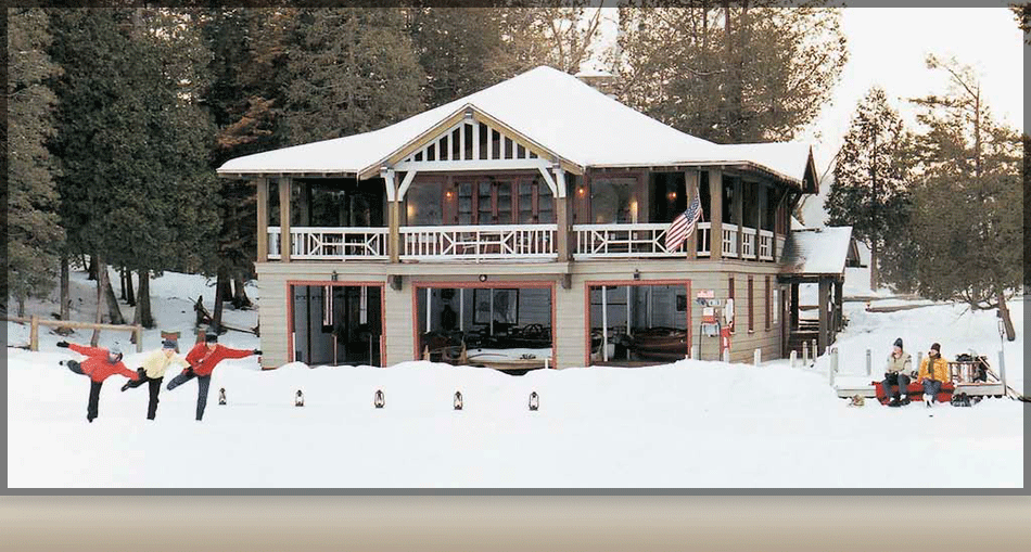 Guests skating on frozen Lake Saranac in front of The Boathouse room at The Point Resort.