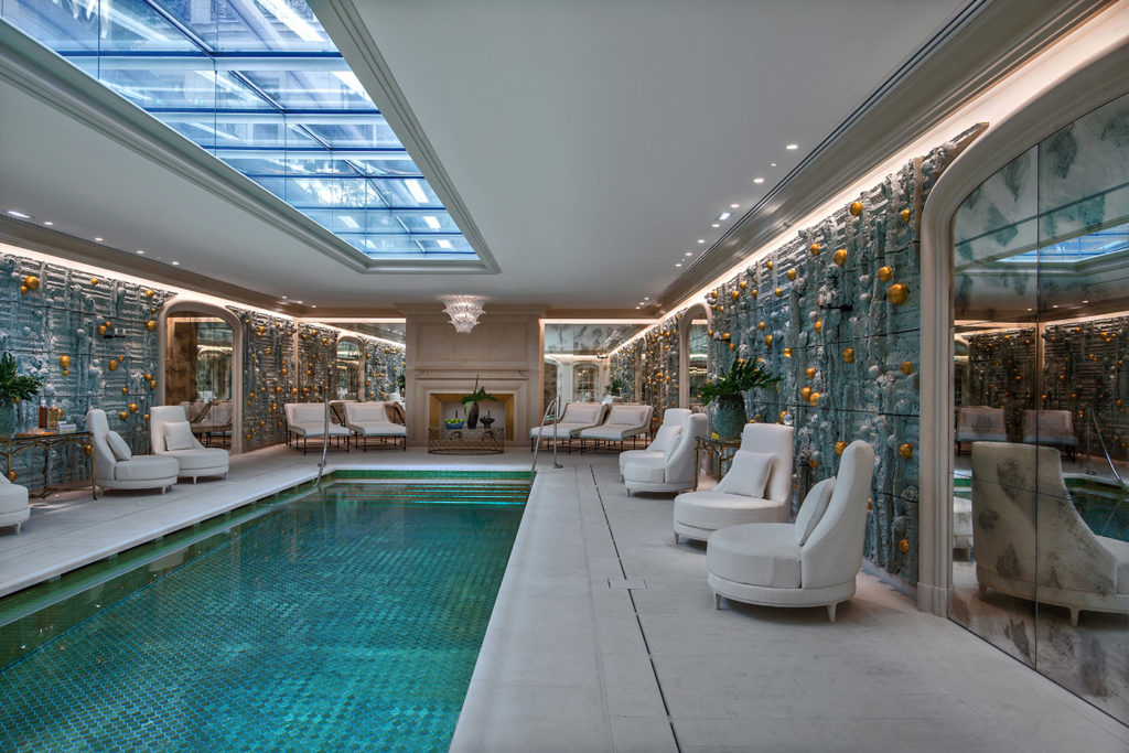 relaxing swimming pool with comfy chairs and a skylight letting in sunlight
