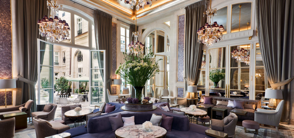 Jardin d'Hiver with purple furnishings, chandeliers, and french doors letting in natural light