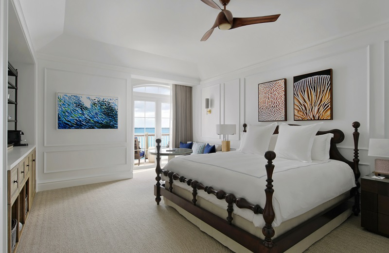 A hotel room at the Rosewood Bermuda hotel featuring a bed, artwork, and a ceiling fan
